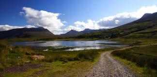 Lago en las montañas y el camino rural Imagen de archivo