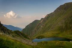 Lago en las montañas y una pequeña nube Foto de archivo