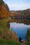 Lago en parque del otoño con el pescador Fotografía de archivo libre de regalías