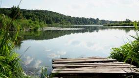 Lago en un día de verano claro contra el bosque, con un embarcadero en el primero plano almacen de metraje de vídeo