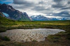 Lago en un valle verde entre las montañas Shevelev Imagen de archivo libre de regalías
