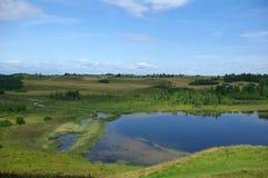 Lago entre las colinas Foto de archivo libre de regalías