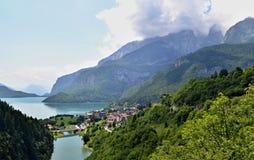 Lago entre montanhas com uma floresta verde no primeiro plano fotografia de stock royalty free