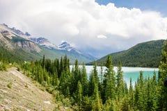 Lago entre picos de montanha e o céu nebuloso Imagens de Stock