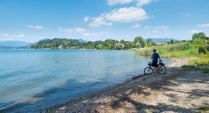 Lago europeo grande Lago Maggiore en Ispra y hombre con la bici, Italia foto de archivo