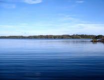 Lago forest sob o céu nebuloso azul, Finlandia Fotografia de Stock