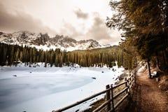 Lago, foresta dell'abete e montagne congelati Lago Carezza nel Tirolo del sud in Italia Fotografia Stock