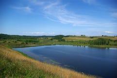 Lago fra le colline Immagini Stock