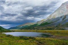 Lago fra le montagne nei precedenti del cielo della tempesta Fotografia Stock