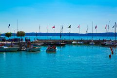 Lago garda, Sirmione, Italia Porto in polizia del lago Bandierine differenti Immagine Stock