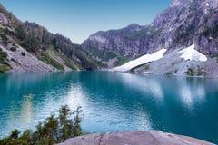 Lago glacier con le montagne e neve durante l'ora legale immagini stock