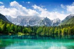 Lago hermoso con las montañas en el fondo