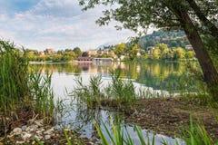 Lago hermoso en Italia septentrional Lago Varese, en el fondo la ciudad de Gavirate con su 'promenade' del lago fotografía de archivo