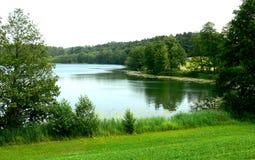 Lago idílico cercado por campos e por prados fotografia de stock