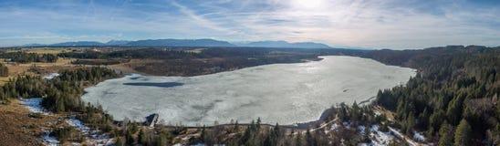 Lago Kirchsee, Baviera, com os cumes no fundo, no inverno da mola fotografia de stock royalty free