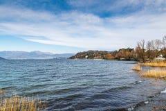 Lago Maggiore, Italia Ispra con el pequeño puerto, paisaje del invierno de la 'promenade' a lo largo del lago imágenes de archivo libres de regalías