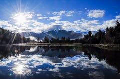 Lago Matheson Reflection por la mañana con la llamarada de Sun Fotografía de archivo