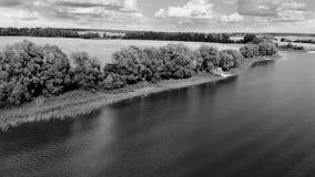 Lago meraviglioso su una penisola contro il cielo blu con le belle nuvole Elaborazione in bianco e nero video d archivio