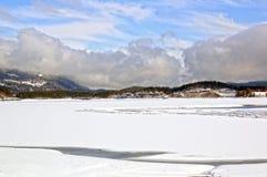 Lago, montañas, bosques y nubes de cúmulo nevados Fotografía de archivo