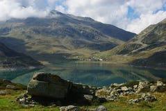 Lago Montespluga con la aldea de Montespluga Fotografía de archivo