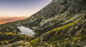 Lago mountain al tramonto con i fiori e la traccia di escursione in Foregro Immagine Stock Libera da Diritti