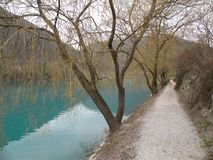 Lago mountain com água azul de turquesa, cercada por cumes e por montes verdes Paz completa A água calma reflete a cidade no coa fotos de stock royalty free
