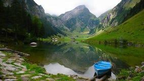 Lago mountain con la barca a remi blu nelle alpi svizzere Immagine Stock