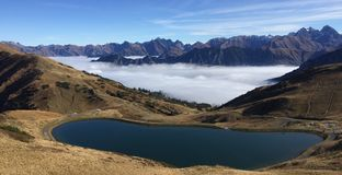 Lago mountain con le montagne e la nebbia nei precedenti immagine stock