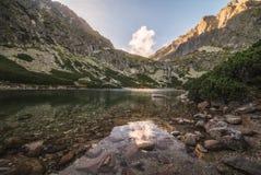 Lago mountain con le rocce in priorità alta al tramonto Fotografia Stock