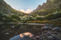 Lago mountain con le rocce in priorità alta al tramonto Fotografia Stock Libera da Diritti