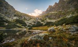 Lago mountain con le rocce in priorità alta al tramonto Immagine Stock Libera da Diritti