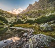Lago mountain con le rocce in priorità alta al tramonto Immagine Stock