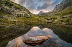 Lago mountain con le rocce in priorità alta al tramonto Fotografie Stock Libere da Diritti