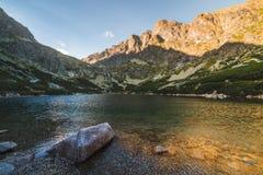Lago mountain con roccia in priorità alta al tramonto Immagini Stock