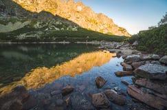 Lago mountain con roccia in priorità alta al tramonto Fotografia Stock Libera da Diritti