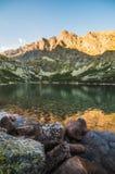 Lago mountain con roccia in priorità alta al tramonto Fotografie Stock