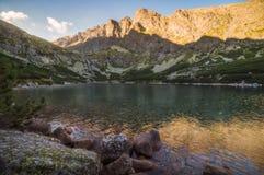 Lago mountain con roccia in priorità alta al tramonto Immagine Stock