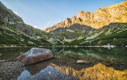 Lago mountain con roccia in priorità alta al tramonto Immagini Stock Libere da Diritti