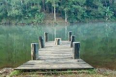 Lago mountain e fiume scorrente con un ponte di legno Fotografia Stock Libera da Diritti