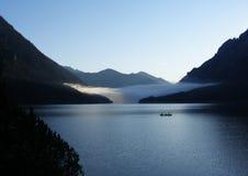 Lago mountain en la puesta del sol con los pescadores en barco Foto de archivo libre de regalías
