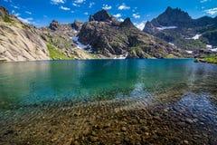 Lago mountain rodeado por las rocas fotos de archivo