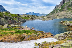 Lago mountain in valle d'attaccatura ed in neve di fusione Fotografie Stock