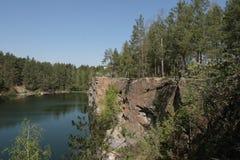 Lago na floresta com precipícios de pedra A pedreira de pedra na floresta balança na perspectiva de um lago da floresta Fotografia de Stock
