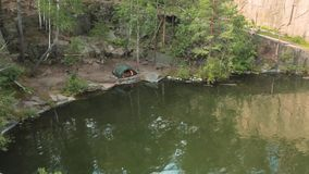 Lago na pedreira de pedra com costas rochosas Lago bonito e árvores verdes ao redor video estoque
