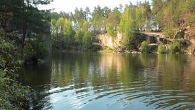 Lago na pedreira de pedra com costas rochosas Lago bonito e árvores verdes ao redor vídeos de arquivo