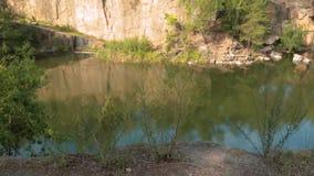 Lago na pedreira de pedra com costas rochosas vento macio que move-se através das árvores finas novas filme
