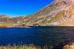 Lago nas montanhas Carpathian, cabine vermelha Balea pelo lago imagem de stock