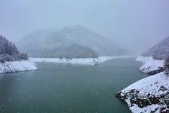 Lago nas montanhas em um dia nevado Imagens de Stock