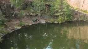 Lago nella cava di pietra con le rive rocciose Bello lago ed alberi verdi intorno archivi video