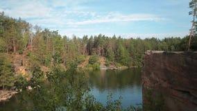 Lago nella cava di pietra con le rive rocciose Bello lago ed alberi verdi intorno video d archivio